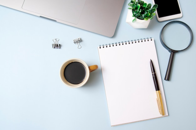Widok z góry obszaru roboczego z makiety notesu, lupa, kawa, laptop na niebieskim tle