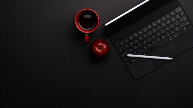 Widok z góry obszaru roboczego z tabletem, klawiaturą, rysikiem, kubkiem do kawy i miejscem na kopię w pokoju biurowym