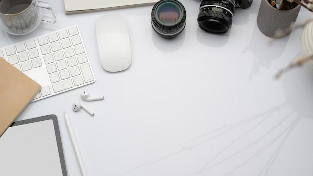 Widok z góry obszaru roboczego z urządzeniami cyfrowymi, aparatem i materiałami biurowymi, układ płaski