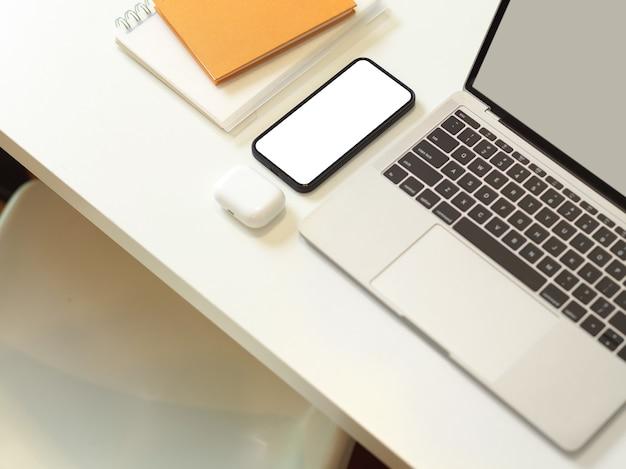 Widok z góry obszaru roboczego ze smartfonem laptopa i papeterią na białym biurku z białym krzesłem w pokoju biurowym