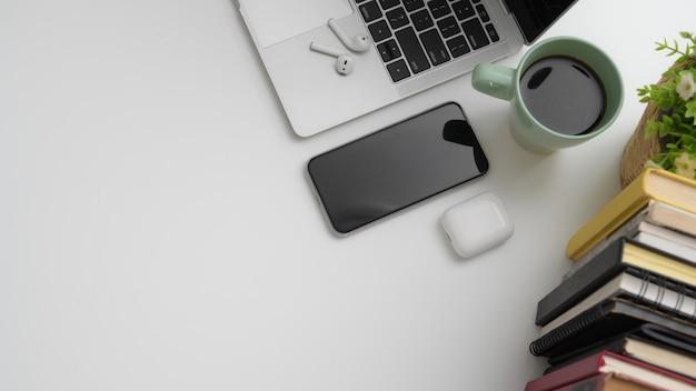Widok z góry obszaru roboczego ze smartfonem, laptopem, książkami, filiżanką kawy i miejsca kopiowania