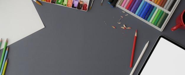 Widok z góry obszaru roboczego ze szkicem papieru, próbką koloru, tabletem, narzędziami do malowania i kopią