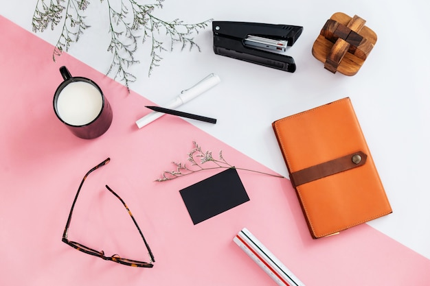 Widok z góry oddziałów kwiatowych, kubek mleka, długopis, ołówek, okulary, zszywacz, notatnik