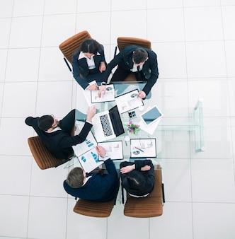 Widok z góry odnoszącego sukcesy zespołu biznesowego omawiającego plany marketingowe i harmonogramy finansowe rozwoju firmy