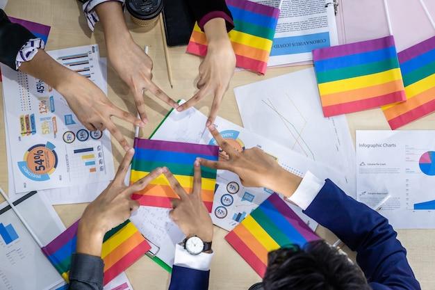 Widok z góry odnoszący sukcesy pracownicy grupa azjatyckich partnerów biznesowych o różnej płci (lgbt) kładąca ręce razem z paper lgbt flag na spotkaniu w pokoju w biurze,
