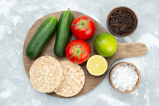 Widok z góry ogórki i pomidory z limonkami i okrągłymi krakersami na szaro