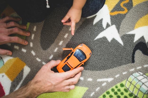 Widok z góry ojciec i syn gra z pomarańczowym samochodzie