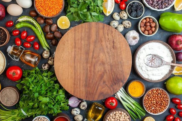 Widok z góry okrągła deska ciasta fasola w misce czosnek cytryna pomidor orzech laskowy granat pietruszka na stole