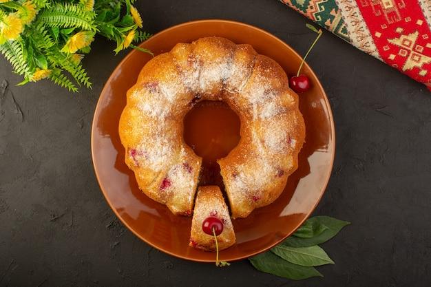 Widok z góry okrągłe ciasto wiśniowe wewnątrz brązowego talerza na ciemnym stole ciasto biszkoptowo-cukrowe słodkie