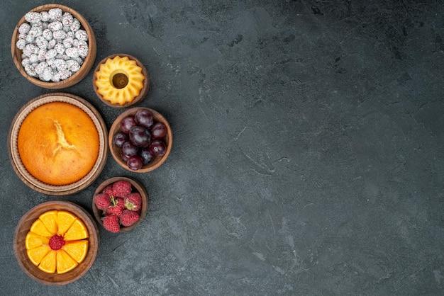 Widok z góry okrągłe ciasto z owocami i cukierkami na ciemnej powierzchni słodkie ciasto owocowe