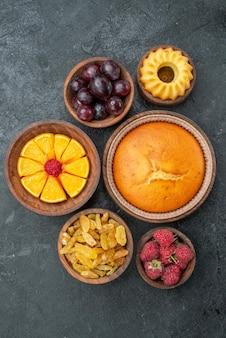 Widok z góry okrągłe ciasto z owocami i cukierkami na ciemnoszarej powierzchni słodki biszkoptowy ciasto owocowe jagoda