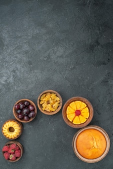 Widok z góry okrągłe ciasto z owocami i rodzynkami na szarej powierzchni słodkie ciasto ciasto owocowe ciastko z jagodami