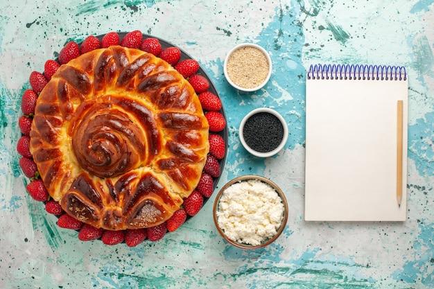 Widok z góry okrągłe pyszne ciasto pieczone i słodkie ciasto na niebieskiej powierzchni