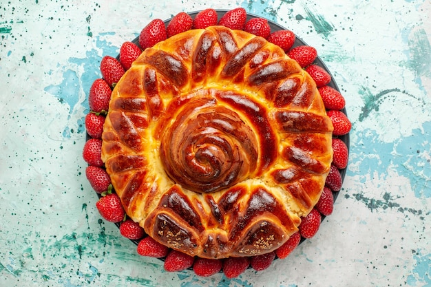 Widok z góry okrągłe pyszne ciasto z czerwonymi truskawkami na jasnoniebieskiej powierzchni