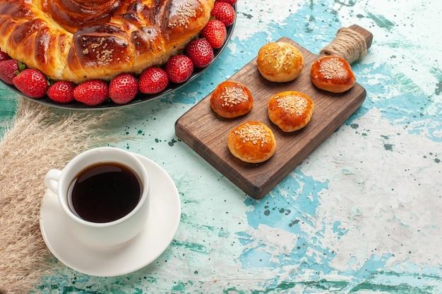 Widok z góry okrągłe pyszne ciasto z truskawkami i filiżanką herbaty na jasnoniebieskiej powierzchni
