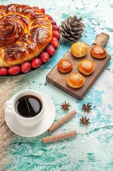 Widok z góry okrągłe pyszne ciasto z truskawkami i filiżanką herbaty na jasnoniebieskim biurku