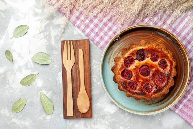 Widok z góry okrągłego ciasta wiśniowego uformowanego wewnątrz na lekkiej, słodkiej herbacie do pieczenia ciasta owocowego