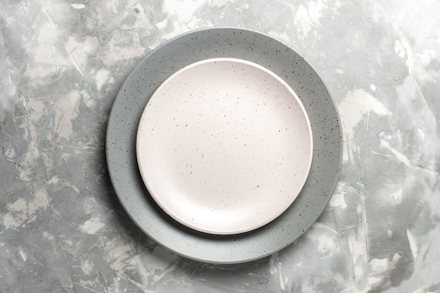 Widok z góry okrągłego pustego talerza w kolorze szarym z białą płytą na szarej powierzchni