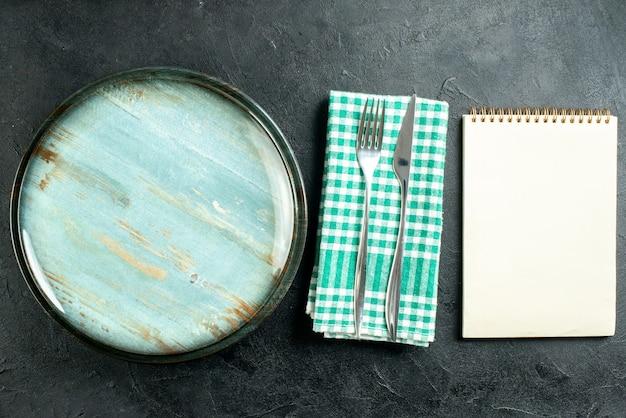Widok z góry okrągły talerz nóż i widelec na zielony i biały notatnik w kratkę serwetka na czarnym stole