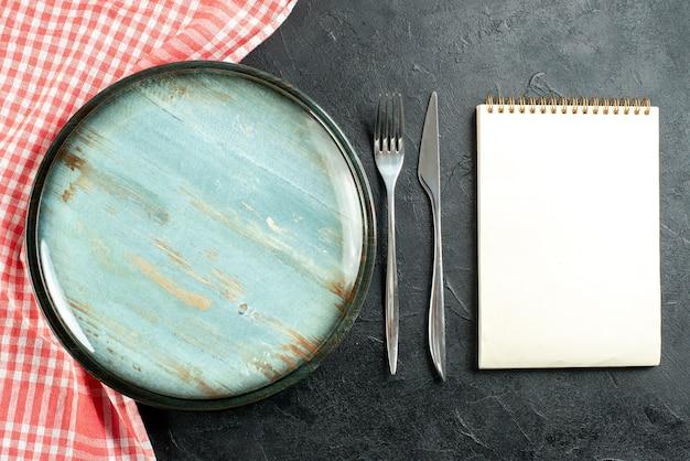 Widok z góry okrągły talerz stalowy widelec i nóż obiadowy czerwony i biały notatnik obrus w kratkę na czarnym stole