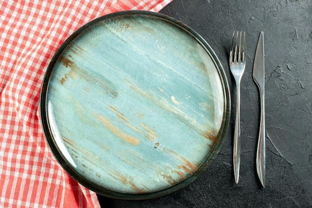 Widok z góry okrągły talerz stalowy widelec i nóż obiadowy czerwony i biały obrus w kratkę na czarnym stole