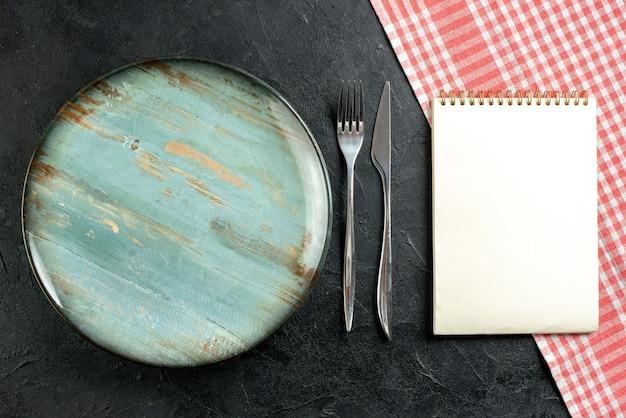 Widok z góry okrągły talerz widelec i nóż obiadowy czerwony i biały notebook obrus w kratkę na czarnym stole