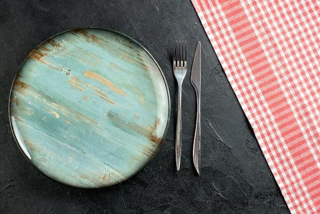 Widok z góry okrągły talerz widelec i nóż obiadowy czerwony i biały obrus w kratkę na czarnym stole