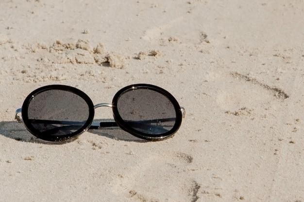 Widok z góry okularów przeciwsłonecznych na plaży w pobliżu błękitnego morza z piaskiem