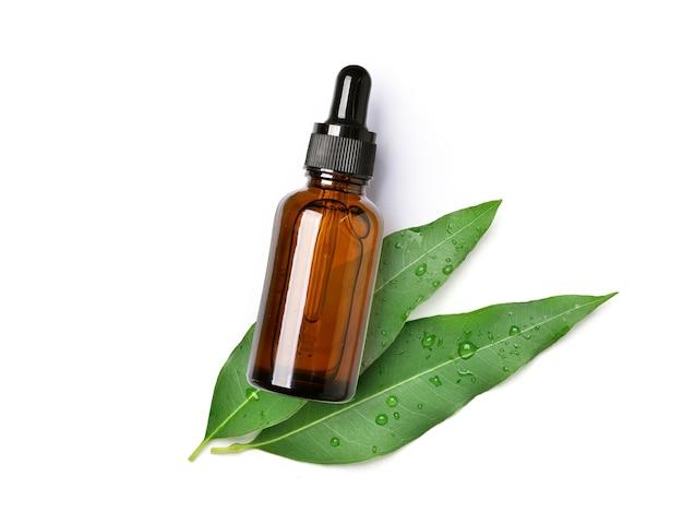 Widok z góry olejku eukaliptusowego w bursztynowej butelce z zakraplaczem z zielonymi liśćmi na białym tle.