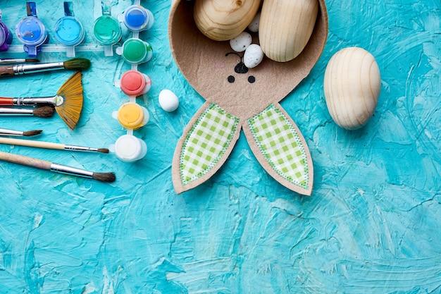 Widok z góry opakowanie jaj z pędzlem, farbą i elementami dekoracyjnymi na niebieskim tle. kopiowanie miejsca, wesołych świąt wielkanocnych, majsterkowania, układanie na płasko.