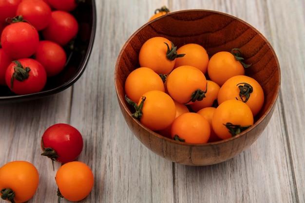 Widok z góry organicznych pomarańczowych pomidorów na drewnianej misce z czerwonymi pomidorami na czarnej misce na szarej drewnianej powierzchni