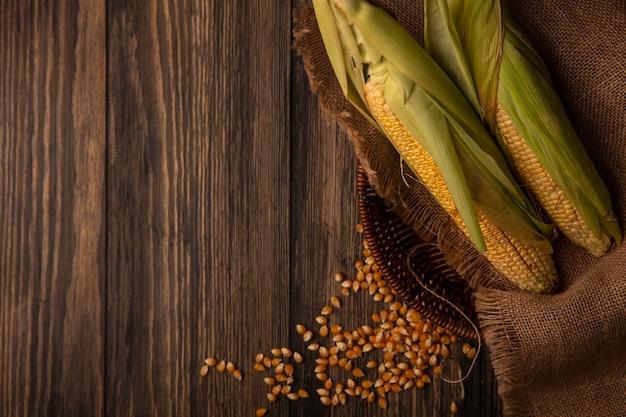 Widok z góry organicznych świeżych kukurydzy z włosami na wiadrze worek z jąder na białym tle na drewnianym stole z miejsca na kopię
