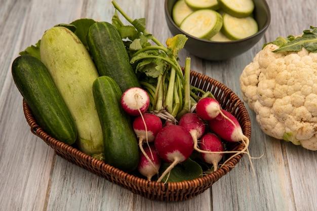 Widok z góry organicznych warzyw, takich jak ogórki, cukinia i rzodkiewki, na wiadrze z kalafiorem na szarym tle drewnianych