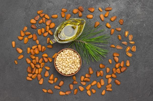 Widok z góry orzeszki piniowe, olej i gałąź cedrowa