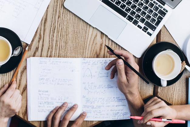 Widok z góry osób studiujących w książce, książce i laptopie. filiżanki kawy na stole