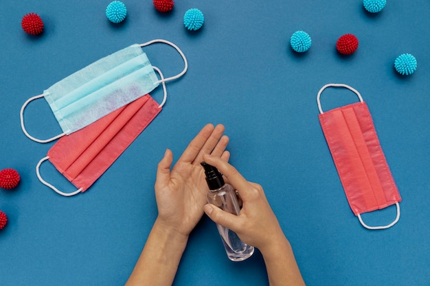 Widok z góry osoba dezynfekująca ręce w pobliżu kolorowych masek medycznych