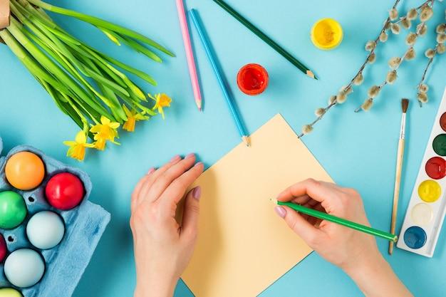 Widok z góry osoby malującej pisanki i pisania kartkę z życzeniami