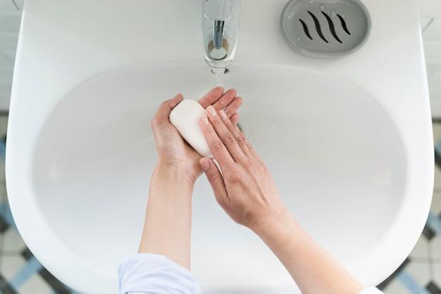 Widok z góry osoby myjącej ręce przy zlewie z mydłem