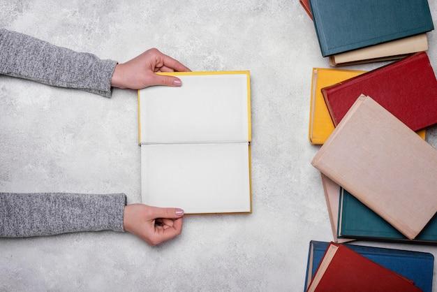 Widok z góry osoby posiadającej otwartą książkę w twardej oprawie
