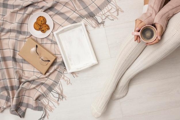 Widok z góry osoby trzymającej kubek kawy z ciasteczkami i tacą