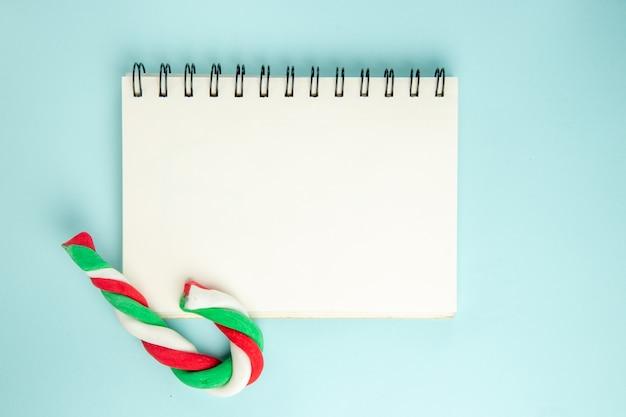 Widok z góry otwartego notatnika z cukierkami na niebieskiej powierzchni