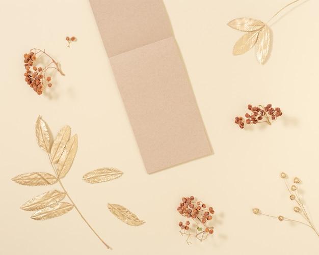 Widok z góry otwartego notatnika z pustymi stronami z papieru rzemieślniczego do pisania notatek ze złotymi i neutralnymi jesiennymi liśćmi