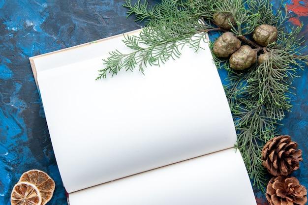 Widok z góry otwarty notatnik gałęzie jodły szyszki choinkowe zabawki na niebieskiej powierzchni