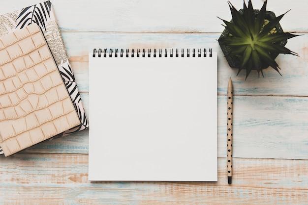 Widok z góry otwarty notatnik, ołówek i roślina doniczkowa na tle drewnianego biurka. pusta strona tekstu biznesowego