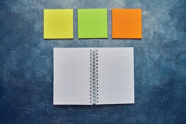 Widok z góry otwarty spiralny pusty notatnik i pusta notatka naklejki na niebieskim tle. powrót do koncepcji szkoły. leżał płasko, kopia przestrzeń