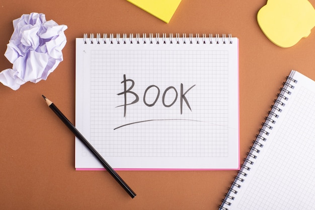 Widok z góry otwarty zeszyt z naklejkami i ołówkiem na brązowym biurku