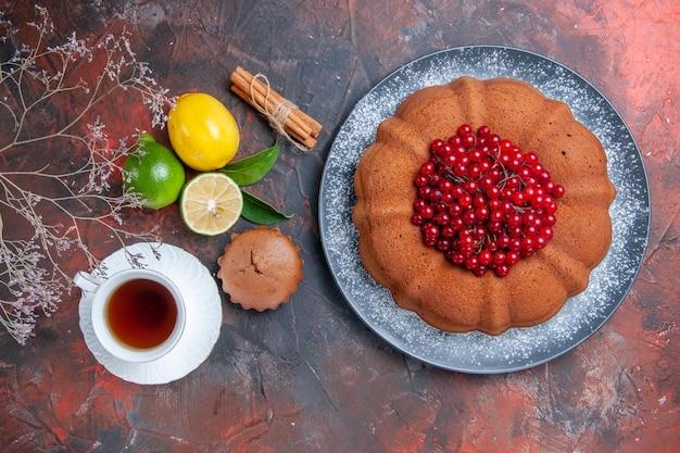 Widok z góry owoce cytrusowe ciasto z jagodami cynamon filiżanka herbaty cytryna babeczka gałązki drzewa