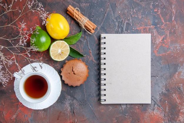 Widok z góry owoce cytrusowe laski cynamonu filiżanka herbaty cytryna limonka ciastko gałęzie zeszyt