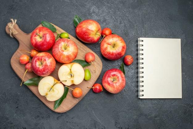 Widok z góry owoce czerwono-żółte jabłka i wiśnie na tablicy obok notesu z jabłkami