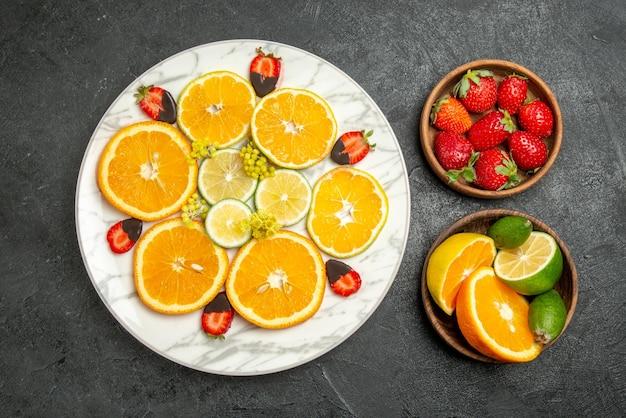 Widok z góry owoce na stole biały talerz truskawek w pomarańczowej czekoladzie oraz cytryny i brązowe miski owoców cytrusowych i jagód na stole